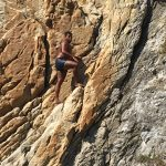 Climbing barefooted up the side of the cliff